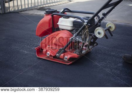 Asphalt Rammer. Laying The Road Surface. Creation Of Parking. The Worker Levels The Road Surface. Ho