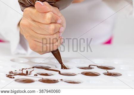 Close-up Chocolatier Pours Hot Dark Chocolate Into Confectionery Mold Using Pastry Bag, Filling Out