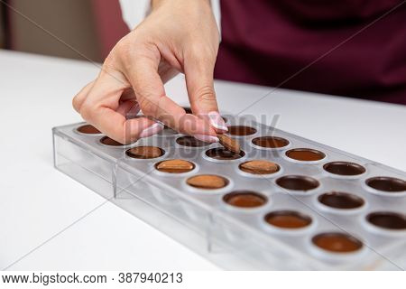Top View Of Confectioner Adding Almonds Into Caramel Filling Chocolate Mold. Chocolatier Preparing L