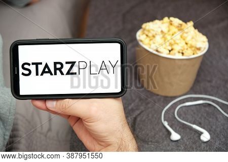 Starz Play Logo On The Mobile Phone Screen With Popcorn Box And Apple Earpods On The Background, Sep