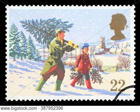 United Kingdom - Circa 1990: A Stamp Printed In The United Kingdom Shows Man Carry Christmas Tree, C