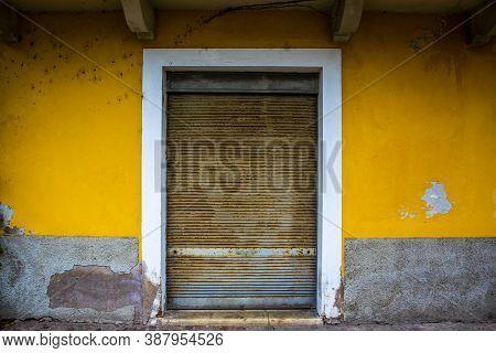 Ancient Rusty Closed Shutter Set In An Ocher Yellow Wall In Riva Del Garda, Trento, Italy