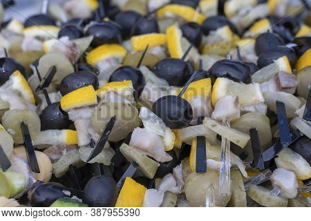 Set Of Delicious Canapes , Closeup. Many Canapes With Black Olives, Cucumber, Lemon, Fat And Meat On