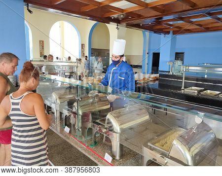 Sharm El Sheikh, Egypt - September 14, 2020: Waiter In Protective Mask Serving Food At Restaurant At
