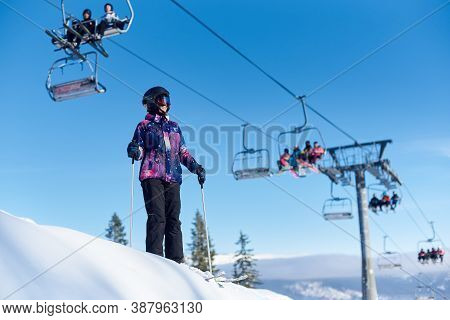 Smiling Skier Woman In Goggles And Helmet Standing On Her Skis With Poles Near Ski Lift In Action. F