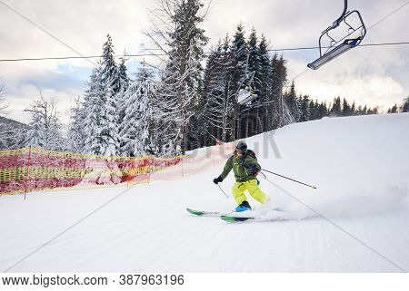 Male Skier Skiing And Carving Turn On Prepared Ski Slope At Ski Resort After Taking Chairlift On Sno