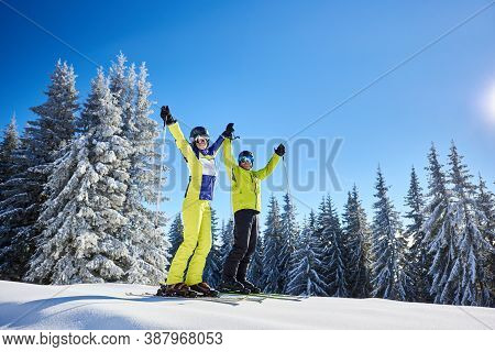 Smiling Woman And Man On Skis With Ski Poles In Hands Up. Exultant Couple At Ski Resort In Sunny Win