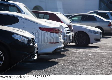 Cars Parked In A Row On A Concrete Site.