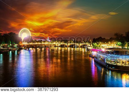 Illuminated Ferris Wheel And River Seine In Paris At Sunset, France