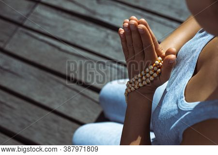 The Young Woman Sitting On A Wooden Pier With Her Hands Folded With A Rosary In A Prayer Pose. Medit