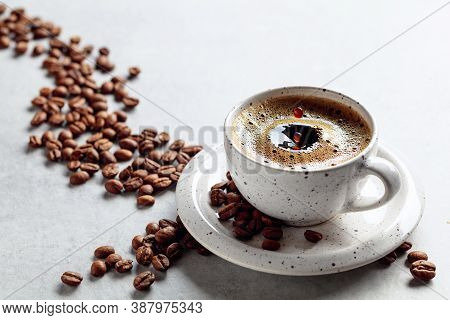 Black Coffee And Coffee Beans On A White Table. A Drop Of Coffee Fall In A Cup. Copy Space.