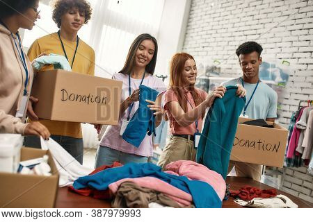 Happy Young Volunteers Group Sorting, Packing Clothes In Cardboard Boxes, Diverse Team Working Toget