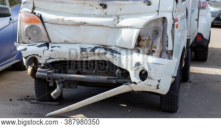 Crashed Car Close-up. The Front Of The Car Is Light Gray, Badly Damaged And Accidentally Smashed On