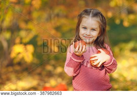 Cute Little Girl In Autumn Park Hold Red Apples In Hands