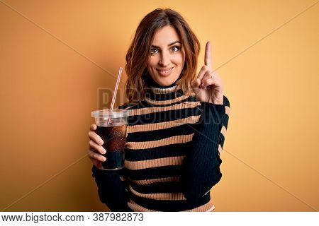 Young beautiful brunette woman drinking glass with cola refreshment using straw surprised with an idea or question pointing finger with happy face, number one