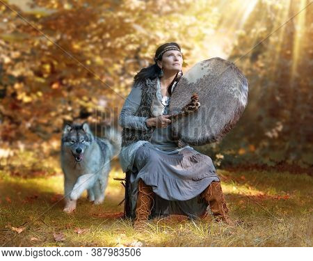 Shaman Woman Playing Her Shaman Sacred Drum In The Forest Against The Background Of Nature, The Big