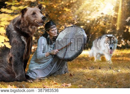 Shaman Woman Playing Her Shaman Sacred Drum In The Forest Among Wild Animals - A Dog And A Bear. Eth