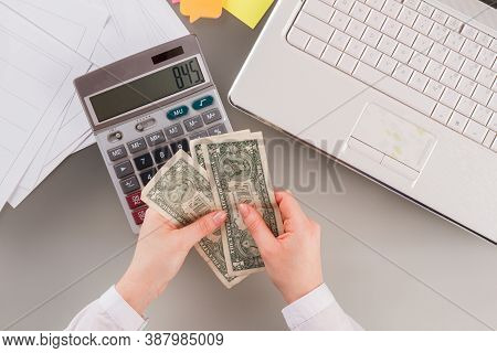 Business Woman Using Calculator And Holding Money. Female Accountant Holding Dollars In Her Hands. A