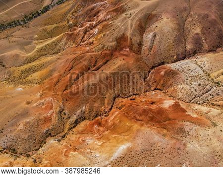 Aerial drone shot of colorful eroded landform of Altai mountains with yellow, brown and red colors.