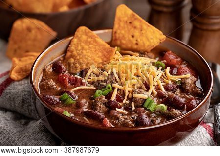 Closeup Of Bowl Of Chili Con Carne With Shredded Ceddar Cheese And Nacho Chips