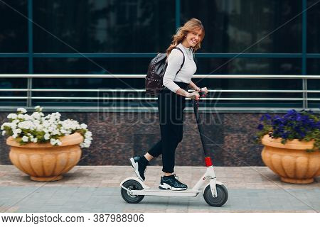 Young Woman Driving Electric Scooter At The City