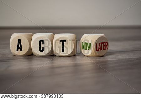 Cubes Dice With Act Now And Act Later On Wooden Background