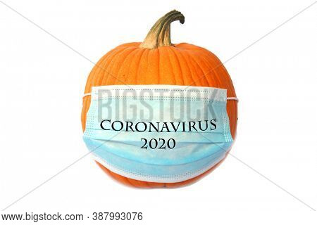 Covid-19 Halloween Pumpkin. Halloween Pumpkin with a Medical Face Mask to represent Coronavirus Caution this Halloween. Face Masks are an important way to stay safe from Covid-19. Isolated on white.