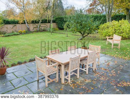 Large Uk Back Garden In Autumn With Wooden Furniture On A Garden Patio Terrace