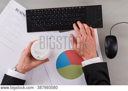 Businessman Holding Coffee Cup While Working On His Project. Male Hand Typing On Computer Keyboard A