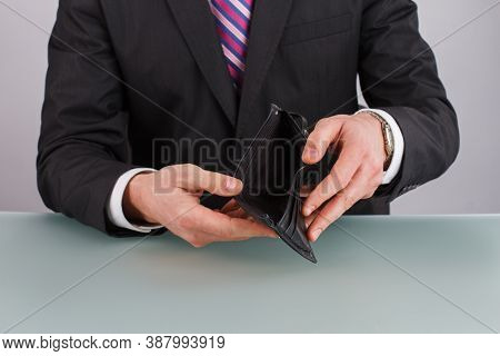 Business Person Holding An Empty Wallet. Broke Businessman. Economic Crisis.