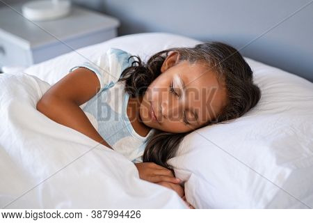 Little cute mixed race girl lying on bed. Portrait of little indian child sleeping under white blanket. Close up face of adorable female kid sleeping deeply and dreaming with closed eyes in bedroom.