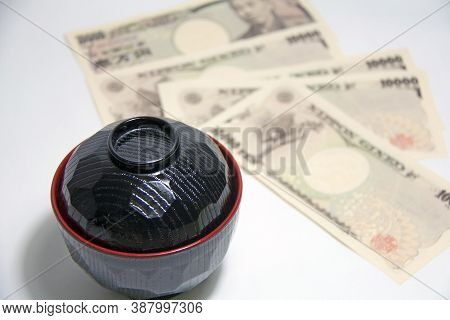 Black Color Red Edge Miso Soup Bowl With Yen Banknotes Of Japan On The White Background. The Concept
