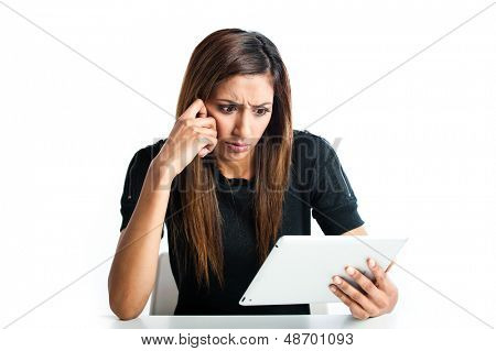 Attractive young Asian Indian teenage woman, working with a non-branded generic portable tablet looking a little confused