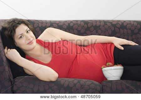 Portrait of a pregnant young woman with bowl of strawberries relaxing on sofa