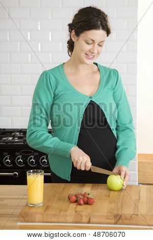 Pregnant young woman preparing cutting fruit in the kitchen at home