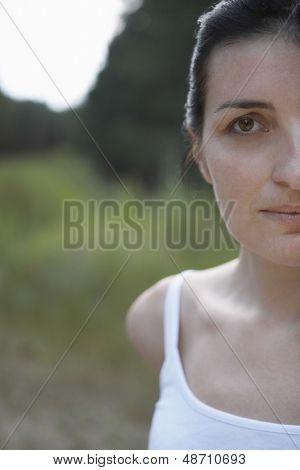 Closeup portrait of a cropped woman in tank top against blurred landscape