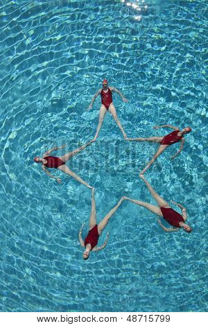 Elevated view of synchronised swimmers forming a star shape in pool