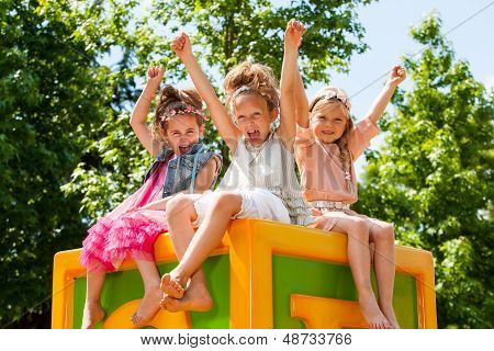 Happy Girls Raising Arms Together In Park.
