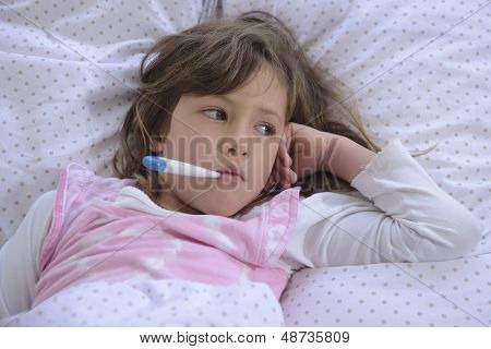 sick girl resting in bed with fever meassuring temperature with thermometer