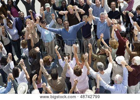 Vista de alto ângulo do homem alegre em meio a pessoas de pé com as mãos levantadas