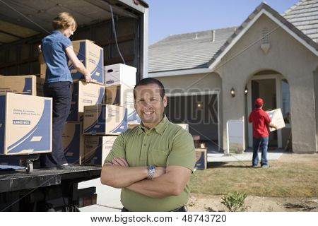 Portrait of a man standing in front of delivery van and new house