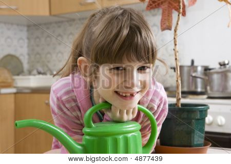 Girl Seven Years Old With Watering-can Sitting On Kitchen