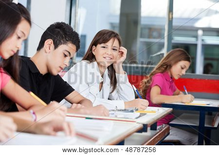 Portrait of beautiful teenage girl with friends writing at desk in classroom