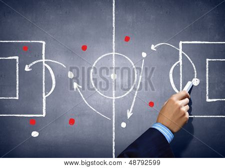 Close up image of human hand drawing football tactic plan