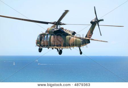 Australian Army Blackhawk chopper flies over the Pacific Ocean. poster