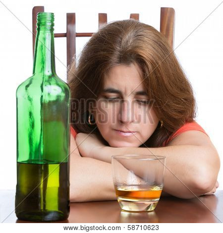 Druk and sad woman with a bottle of scotch isolated on a white background