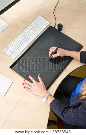 Woman with red finger nails working behind a grapic tablet, busy with computer aided design
