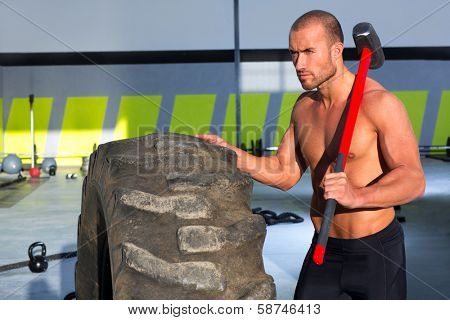 Crossfit sledge hammer man workout at gym relaxed after exercise