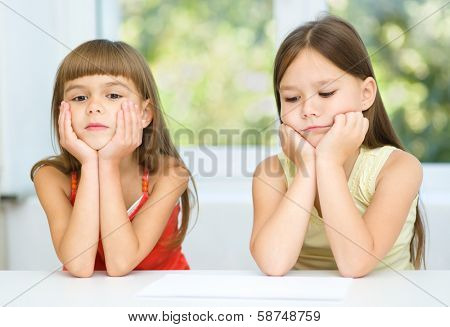 Portrait of two sad little girls are sitting at table