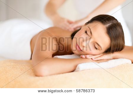 poster of health, beauty, resort and relaxation concept - beautiful woman with closed eyes in spa salon getting massage